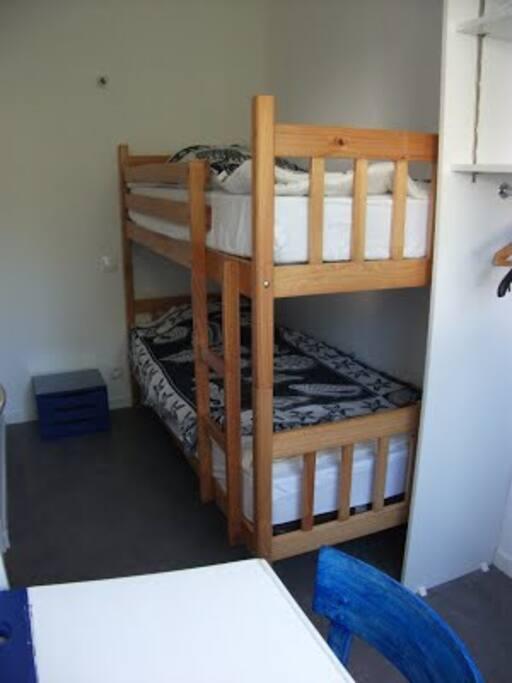 Chambre enfant avec 2 lits superposés, bureau et placard. Cette chambre peut acceuillir un seul lit parapluie supplémentaire (non fourni). 2 couettes de 90x190,  housses non fournies.