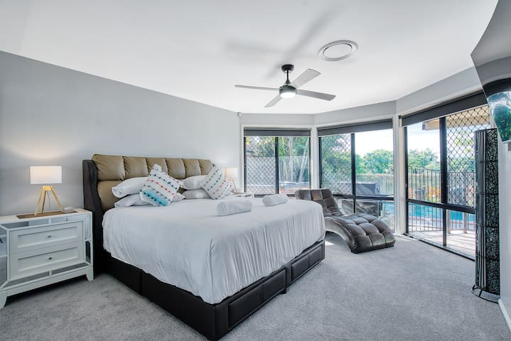 A master bedroom has a plush king bed, leather lounger, and wall-mounted TV framed by large windows offering pool views; as well as an ensuite bathroom.