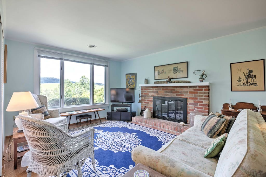 The cozy living room offers a gas fireplace, flat-screen Satellite TV, and fantastic views of the surrounding rolling hills.