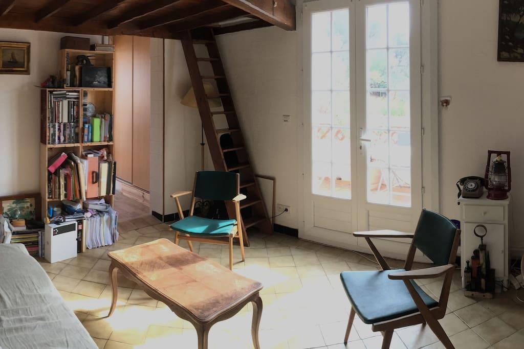 Salon qui donne accès à la grande terrasse par la porte fenêtre. L'escalier en bois mène à la mezzanine.