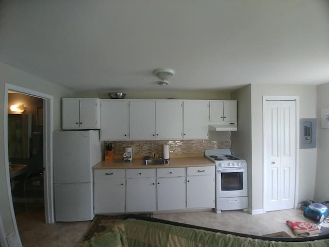 kitchen including coffee maker, microwave, full stove and fridge