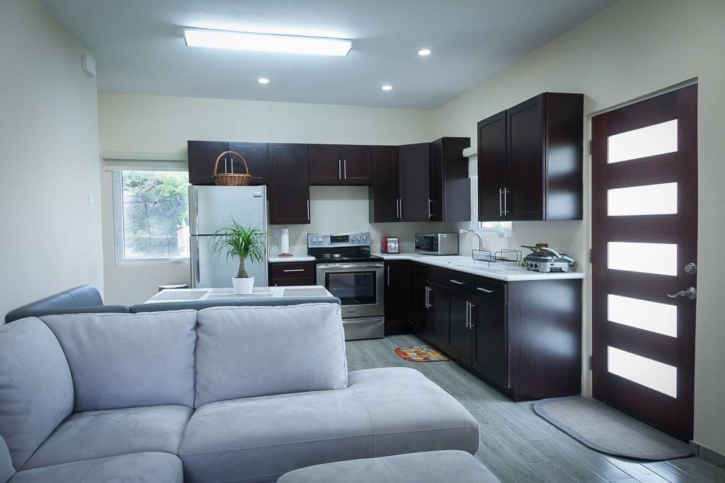 Open plan features kitchen, dining area and family room. The kitchen has a full sized fridge, stove, microwave, coffee maker, electric kettle and toaster.