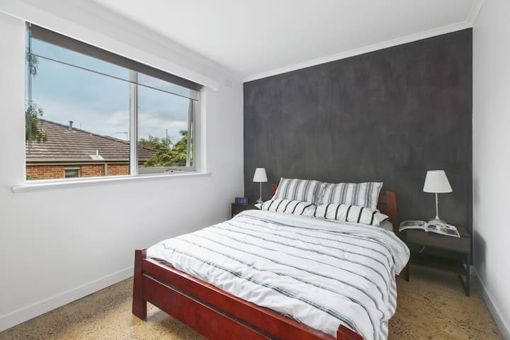 A master bedroom offers a plush queen bed, bedside table and built-in mirrored wardrobes as well as a tallboy and both sheer and black-out blinds