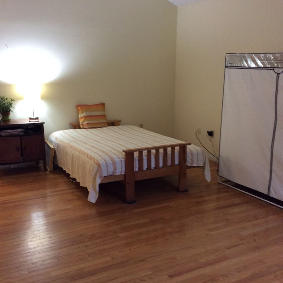 A full-size bed with a large night-stand.