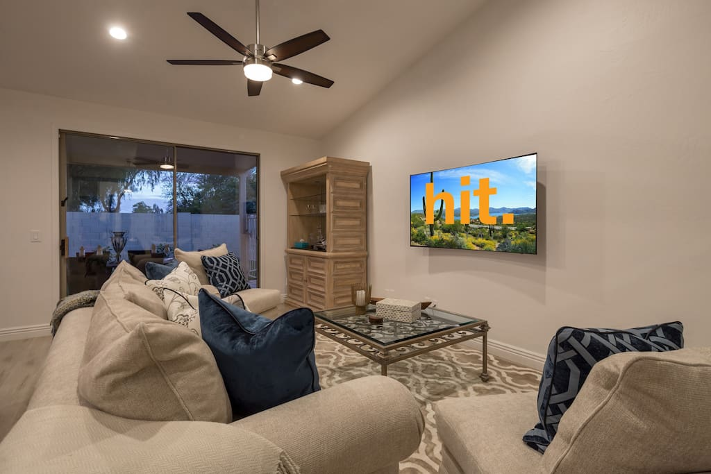 """Living room with cush seating and curved 62"""" TV"""