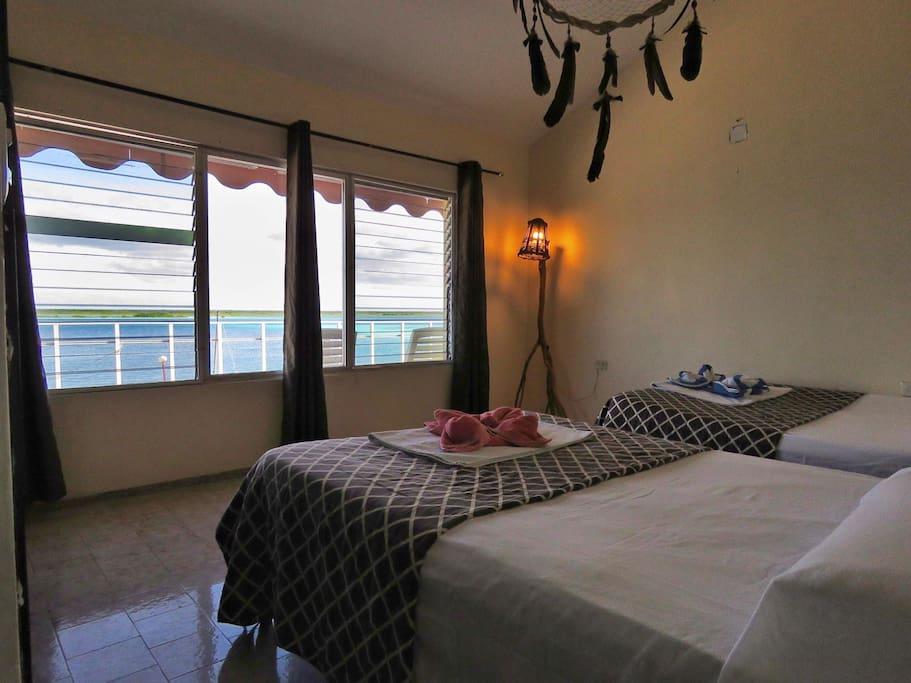 Habitación con dos camas matrimoniales, baño privado, ventiladores, y las bella vista a la laguna y sus amaneceres.