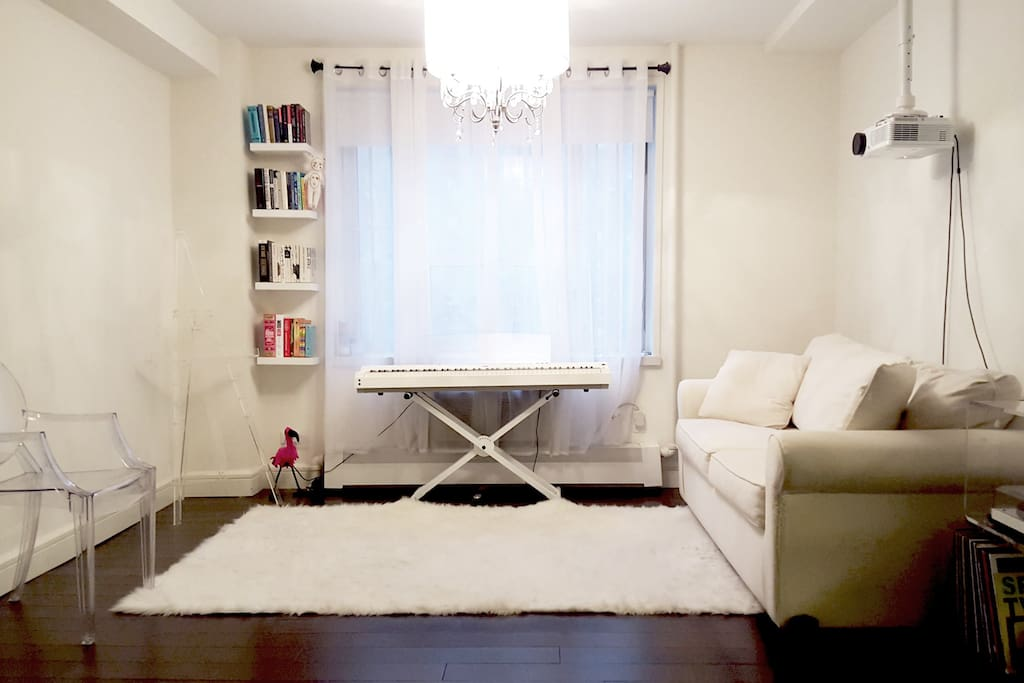 living space with keyboard, movie projector, and sofa-bed. converts into guest bedroom