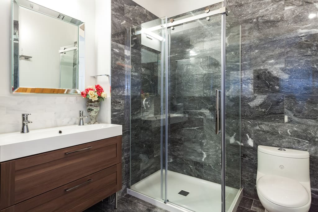 Marble floors and walls, corner walk-in shower with glass sliding bypass entry and grey gloss stacking washer & dryer definitely make this bathroom luxurious.