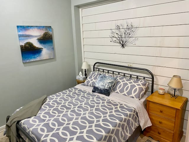 Bedroom with brand new queen bed and bed frame. Large closet, two night stands and a small dresser are provided.