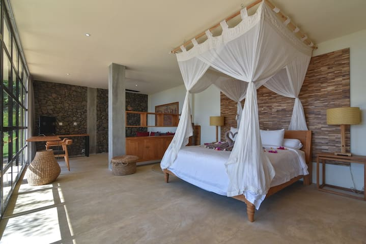 Large Master bedroom on the pool level, with a desk, couch an tv