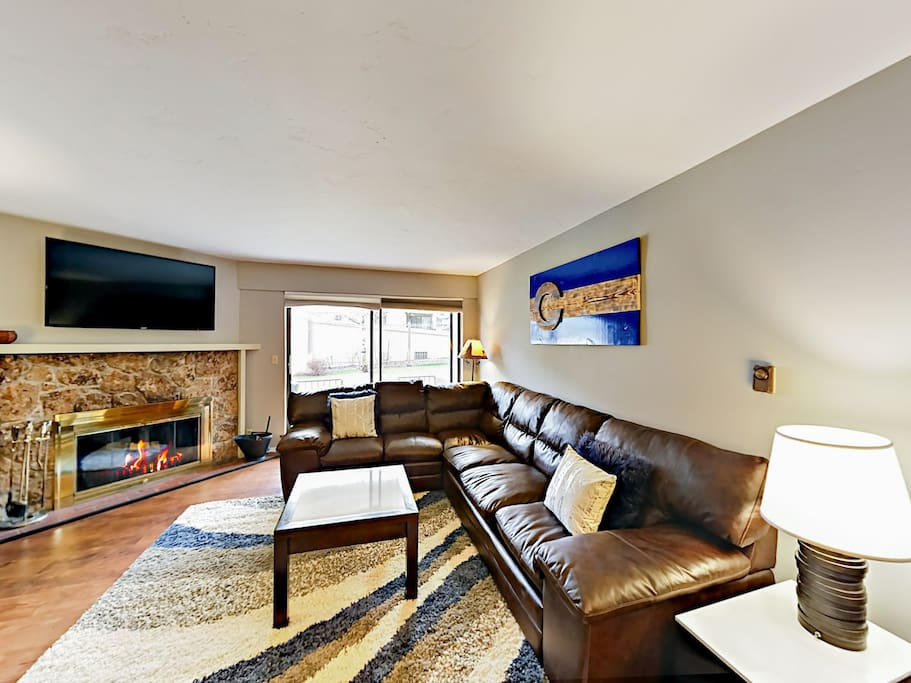 """Enjoy the warm ambiance of the wood-burning fireplace while watching a favorite film on the 55"""" flat screen TV in the living room."""