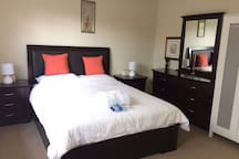 First room, Specious queen bedroom with reverse Aircon, TV, dressing table and wardrobe
