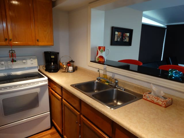 Private kitchen with stove, oven, coffee maker, dishes and fridge