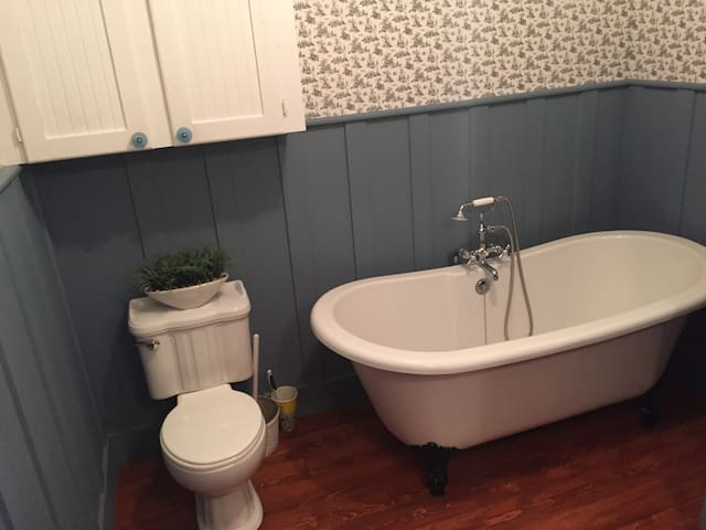 Downstairs bath with large clawfoot soaker tub