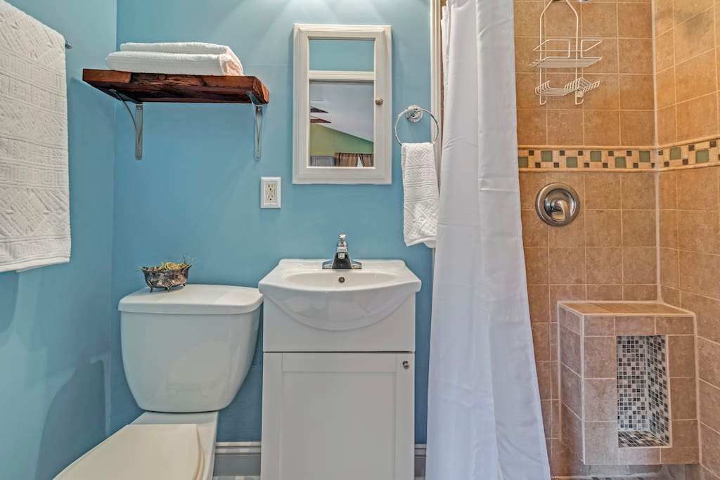 Clean and convenient bathroom with tile floor and shower with all essentials.