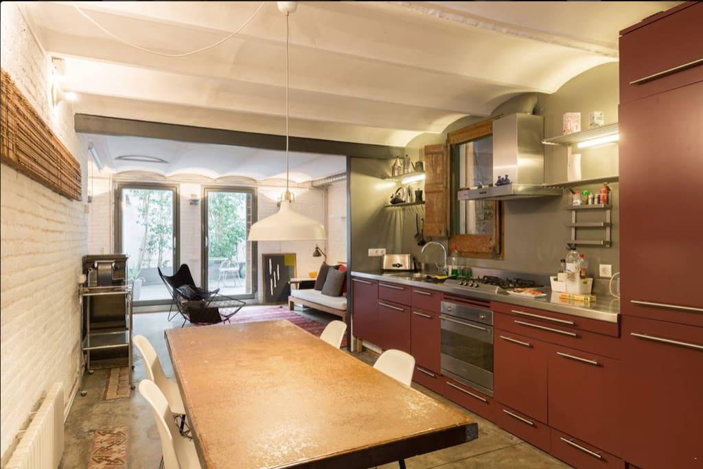 Vista más amplia con la cocina en primer término y el salón y terraza al fondo