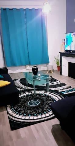 Salon télé écran plat avec  une petite table et deux canapés