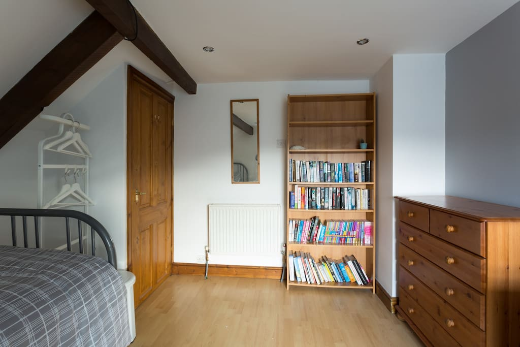 Large single bedroom on 2nd Floor showing hanging space,  mirror, bookcase and drawers
