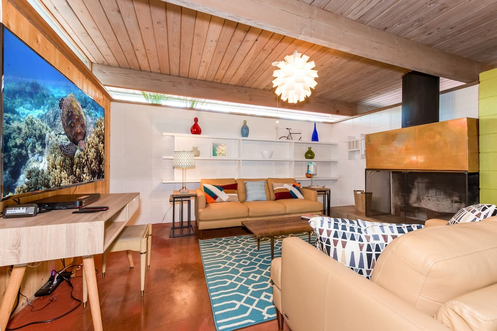 """The main living area has two leather couches and a 60"""" flat screen TV."""