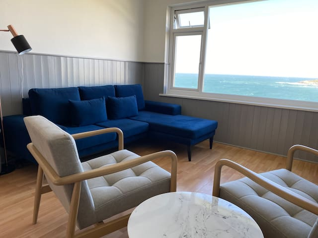 Surf Break Lounge - with some of the best and most breathtaking views in Cornwall - on a clear day like this, with views to Trevose Head 3-seater L-shaped velvet sofa (MADE.com), scandi inspired wide armchairs, coffee table, smart TV with Netflix etc