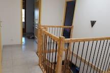 Le hall d'entrée donnant sur trois chambres et la descente d'escalier pour le rez de jardin.