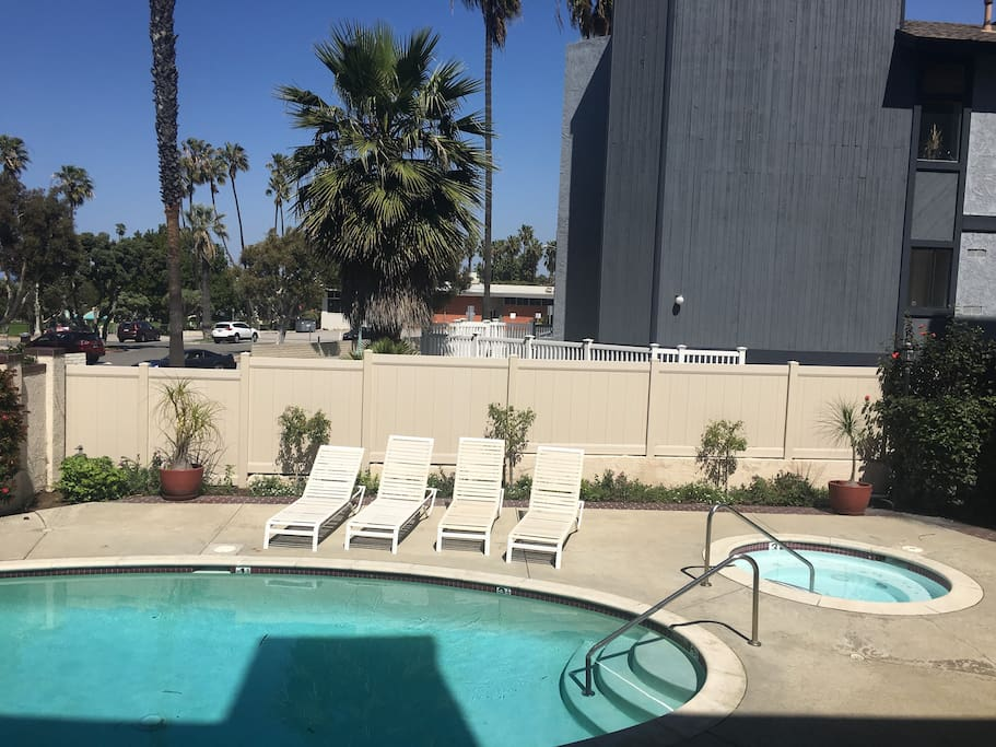 Swimming pool and hot tub, nice pool deck, with loungers, chairs and tables.