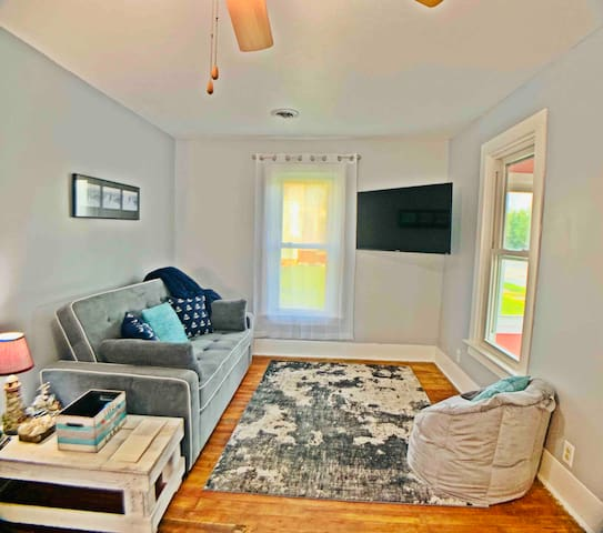 """Family room with queen Serta pull out sofa bed, bean bag chair, 50"""" Roku TV, and a comfy place to curl up to watch movies!"""