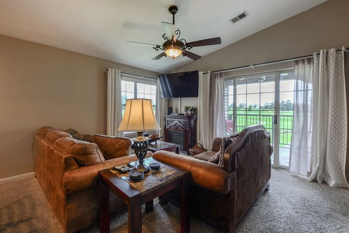 Living area with Fireplace and TV looking out over the Golf Course