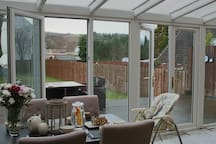 Conservatory looks onto decking and long garden with views of Stoney Mullen Hill beyond.