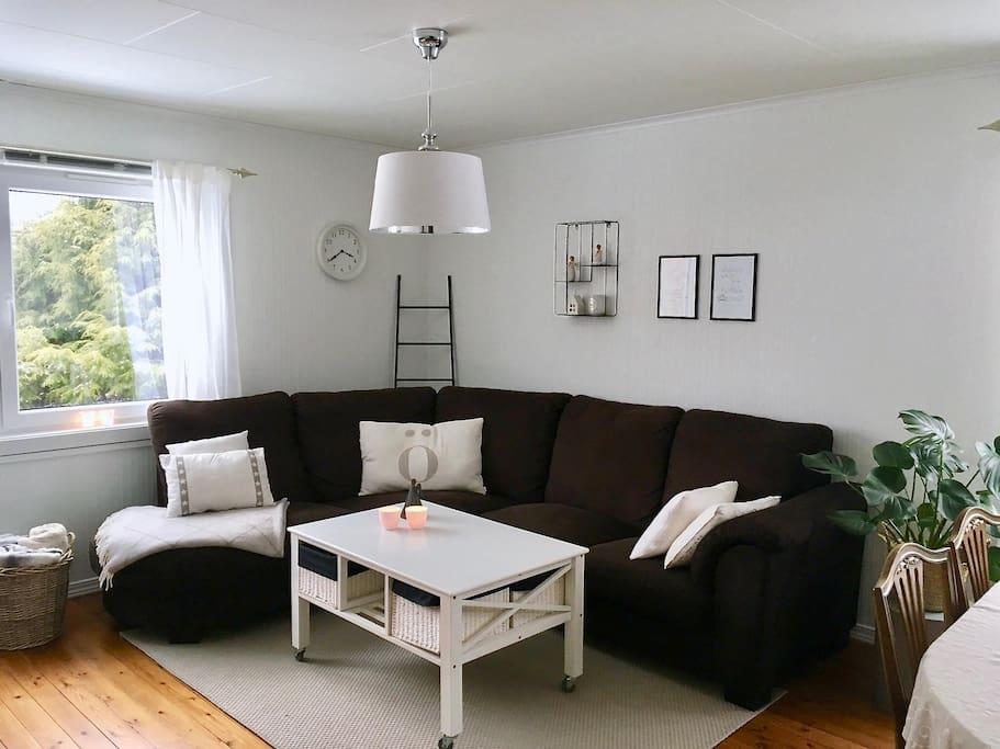 Stue med sofa, TV, spisebord og vedovn.