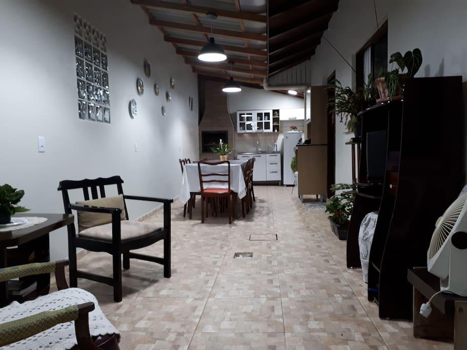 Área de festa compartilhada, com TV, cozinha completa e churrasqueira
