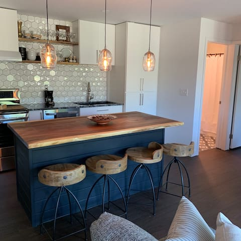 The kitchen has a live edge wood countertop on the custom made island with one of a kind pendants.