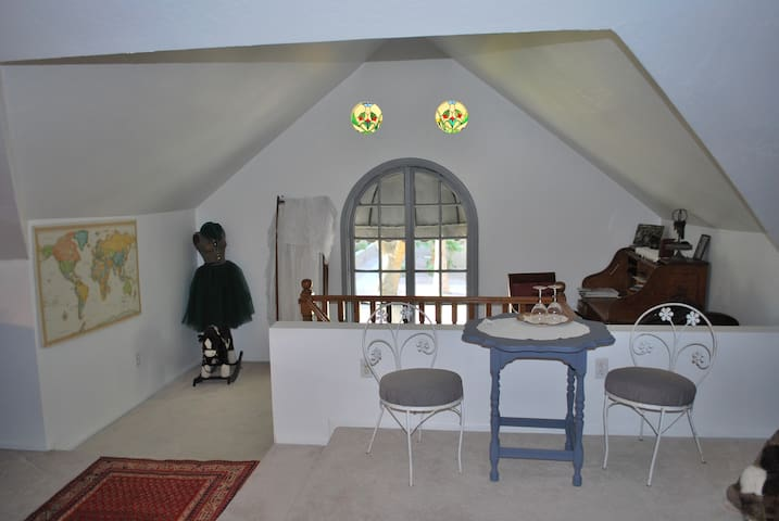 Arched window, colored glass windows, desk area and small cafe table and chairs.