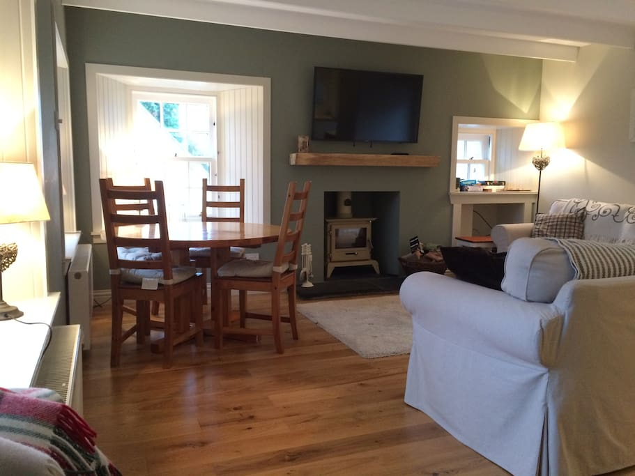"""Living room with wood burner and 48"""" smart TV. Free Wifi"""