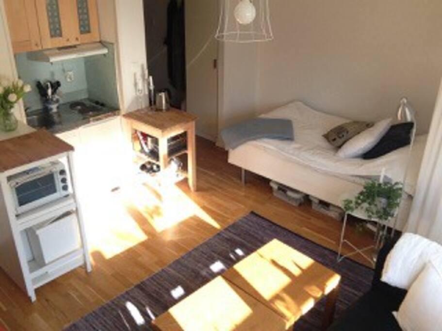 Köksvrå med två kokplattor, liten kyl och frys.