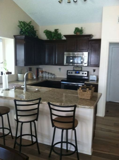 Kitchen with large, granite countertop, new appliances.