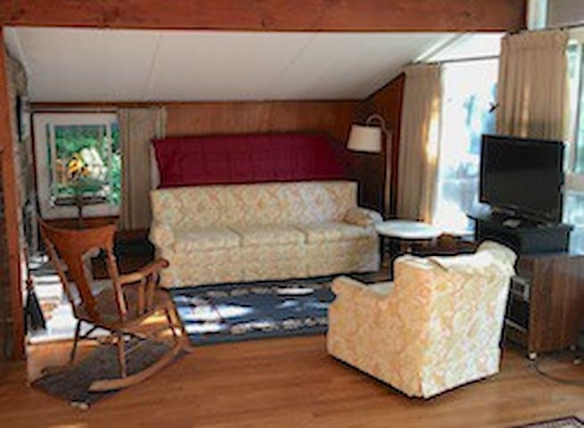 Living room has a sofa and there are single and double matrices stored behind the sofa for extra guests.