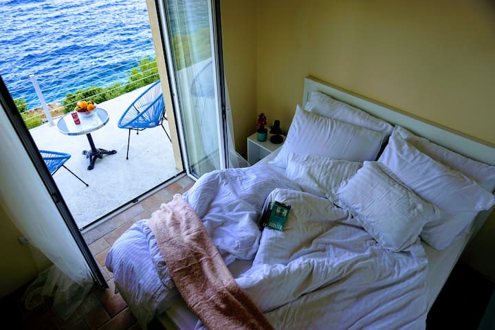 Bedroom #1 with a double bed, great sea view and direct access to the sunny terrace infront of the villa.