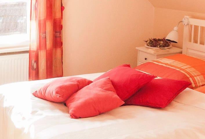 Das Schlafzimmer: Vogelzwitschern, Kiefernrauschen. Urlaub. Ein heller, freundlicher Raum mit großem Doppelbett.