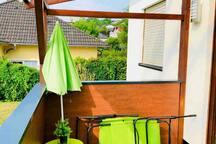 Terrasse mit zwei Liegestühlen und Sonnenschirm