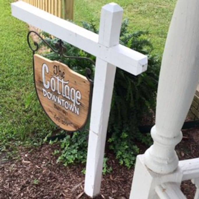 Local Artist DEMO painted this red cypress sign just for The Cottage Downtown! See all of his work all over Breaux Bridge!