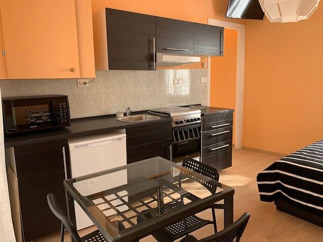 Cucina con frigorifero/freezer, forno microonde e piano cottura con forno tradizionale.