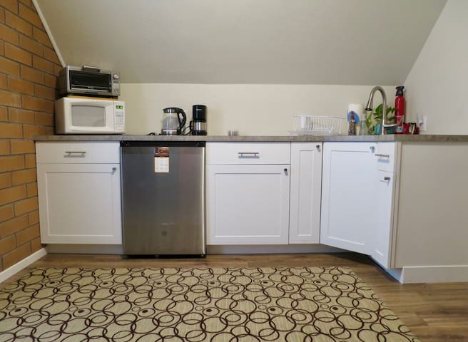 Kitchenette includes microwave, toaster oven, hot water kettle, coffee maker, refrigerator, mugs, plates & bowls, utensils, stainless sink and dish rack.