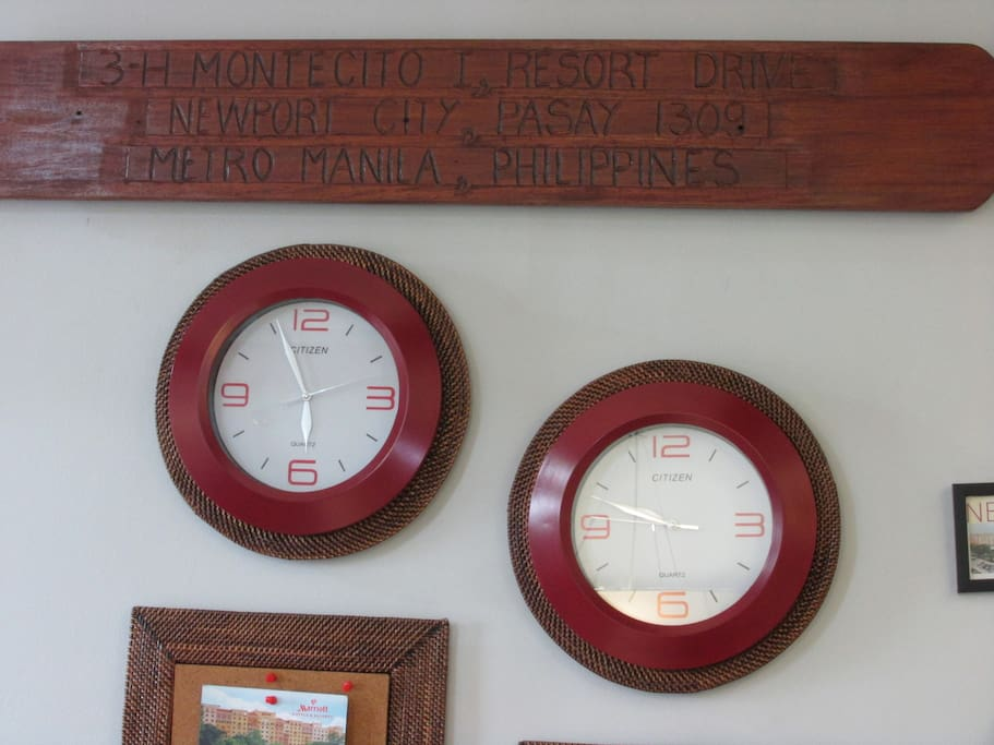 the complete address carved on old wood. visible are 2 wall clocks one for local time and the other where the heart is.
