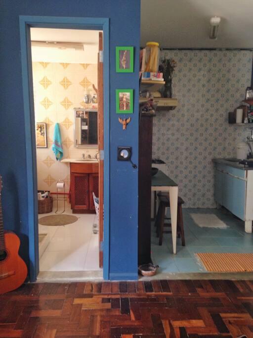 cozinha aberta e banheiro claro.