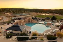 View of Zion Ponderosa Resort pools, hot tubs, grass field, tennis courts, pickle ball courts and paddle board pond.