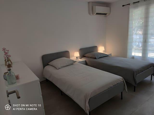 Chambre 4 climatisée 2 lits simples en 90 pouvant être regroupé avec tables et lampes de chevets