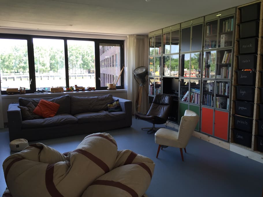 """Living room, good views over the river, park and Rotterdam's famous """"Euromast"""" tower. Sit and watch the boats go by.  Enjoy our books and -for kids- the toys"""
