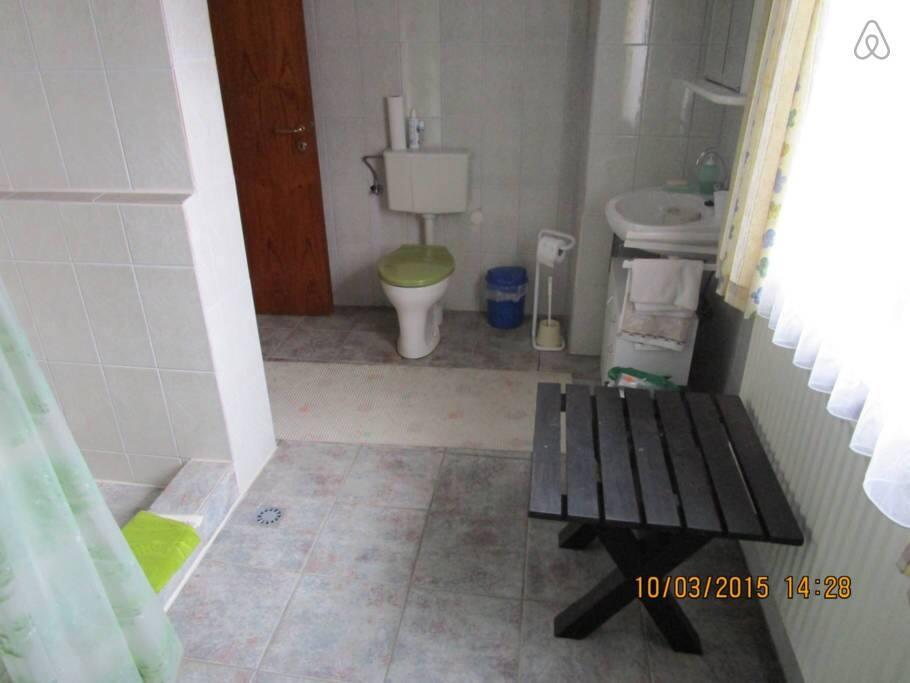 Eigenes Tageslichtbad mit gemauerter Dusche, Waschbecken und WC.