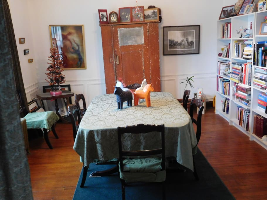 Formal dining room. A variety of games are in the cupboard and many art books are on the shelves.